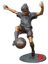 Bronze guy sculpture playing a football In garden
