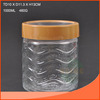Storage clear glass jar with a wave pattern and the lid of plastic and metal